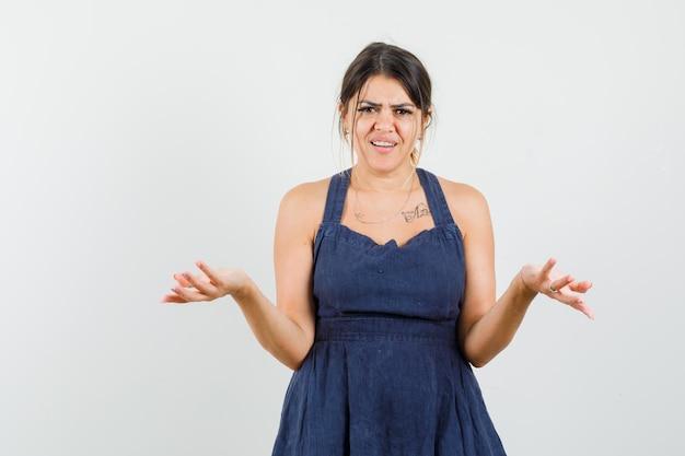 Młoda kobieta w sukience wyciąga ręce na bok, by zapytać o opinię