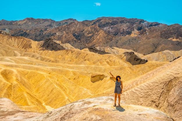 Młoda kobieta w sukience z widokiem na zabriskie point w kalifornii. stany zjednoczone