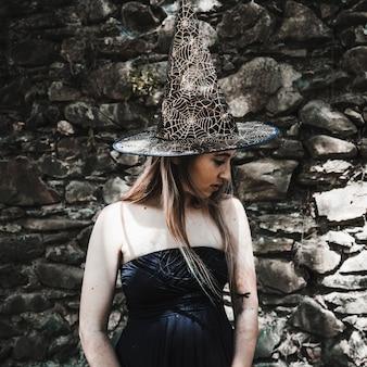 Młoda kobieta w sukni i czarownicy kapeluszowy patrzeć na boku