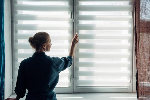 Młoda kobieta w sukni stoi w pobliżu okna z żaluzjami