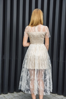 Młoda kobieta w sukni wieczorowej pozowanie na ulicy miasta, ciemne tło ściany
