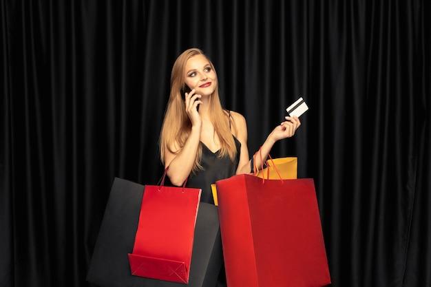 Młoda kobieta w sukni zakupy na czarnej ścianie