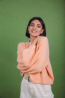 Młoda kobieta w sweter brzoskwiniowy dorywczo na białym tle na ścianie zielonego koloru oliwek
