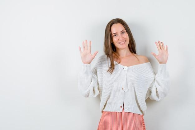 Młoda kobieta w sweter i spódnica pokazuje dłonie w geście kapitulacji na białym tle