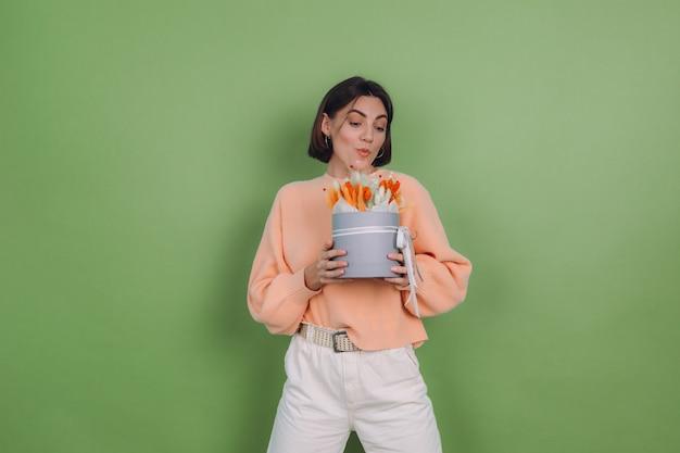 Młoda kobieta w sweter z brzoskwiniami na białym tle na zielonej ścianie oliwek