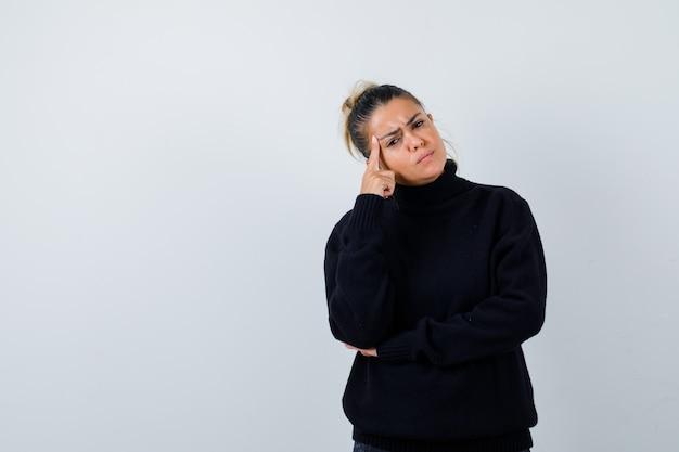 Młoda kobieta w sweter z golfem, stojąc w myśleniu poza i patrząc zamyślony, widok z przodu.