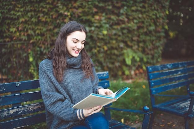 Młoda kobieta w swetrze czytając książkę, siedząc na ławce w parku. za