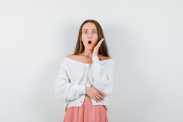 Młoda kobieta w swetrze i spódnicy, trzymając podniesioną rękę w pobliżu otwartych ust na białym tle