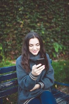 Młoda kobieta w swetrze trzymając inteligentny telefon, siedząc na ławce w parku.