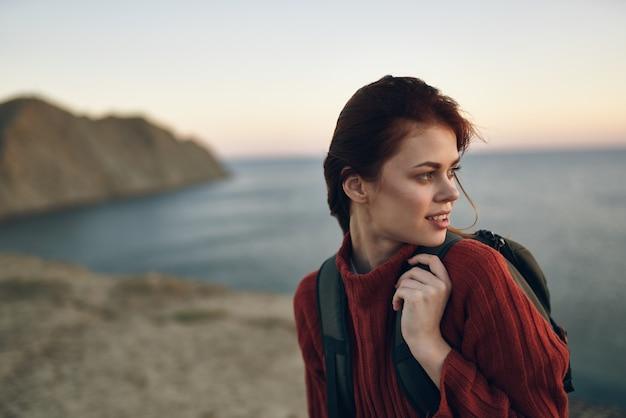Młoda kobieta w swetrze z plecakiem na plecach nad brzegiem morza w górach
