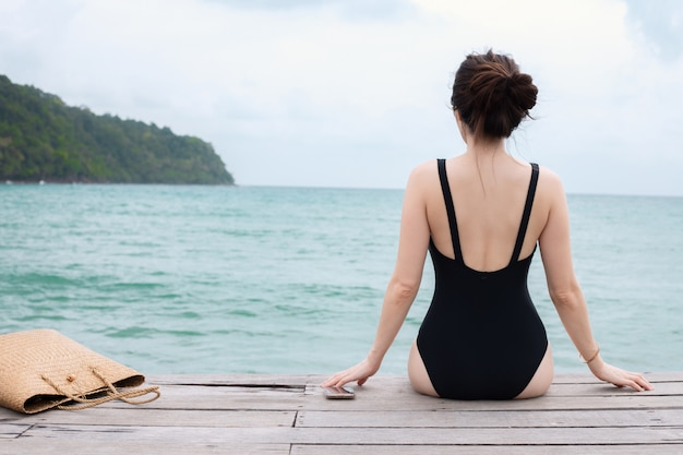 Młoda kobieta w swimsuit opalać się na molo plaży przy morzem, wakacje letni pojęcie.