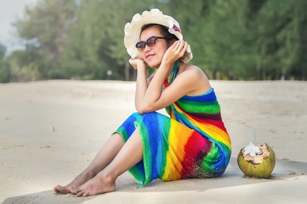 Młoda kobieta w swimsuit z kokosowym koktajlem na plaży, bali
