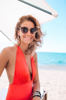 Młoda kobieta w swimsuit z koktajlu szkłem na biel plaży obsiadaniu na sunbed