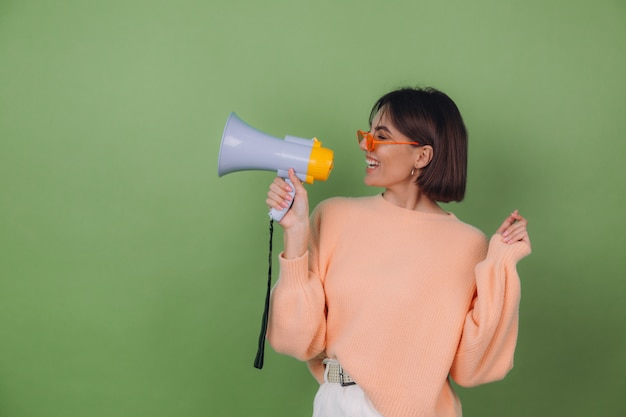 Młoda kobieta w swobodnym brzoskwiniowym i pomarańczowym swetrze z okularami na białym tle na zielonej ścianie z oliwek szczęśliwa krzyczy w przestrzeni kopii megafonu