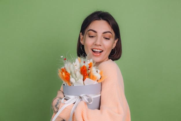 Młoda kobieta w swobodnym brzoskwiniowym swetrze na białym tle na ścianie z zielonymi oliwkami trzyma pomarańczowo-białą kompozycję kwiatów bawełny gypsophila pszenicy i lagurusa na prezent szczęśliwy zdumiony zaskoczony