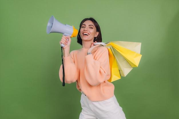 Młoda kobieta w swobodnym brzoskwiniowym swetrze na białym tle na zielonej oliwkowej ścianie krzyczy w megafonie trzymającym torby na zakupy, ogłasza promocję sprzedaży rabatów