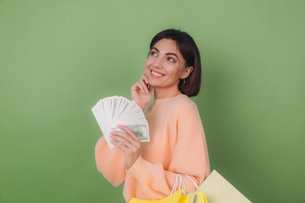 Młoda kobieta w swobodnym brzoskwiniowym swetrze na białym tle na zielonej ścianie z oliwek, trzymająca wachlarza rachunków za 100 dolarów pieniądze i torby na zakupy, myśląca pozytywnie, uśmiechnięta przestrzeń kopii