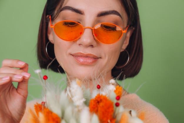 Młoda kobieta w swobodnym brzoskwiniowym swetrze odizolowana na zielonej ścianie z oliwek trzyma pomarańczowo-białą kompozycję kwiatów bawełny, łyszczec, pszenicy i laguru na prezent szczęśliwy zaskoczony