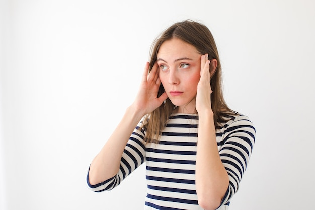 Młoda kobieta w swobodnym pasiastym ubraniu, mając ból głowy i pocieranie skroni, stojąc na białym tle
