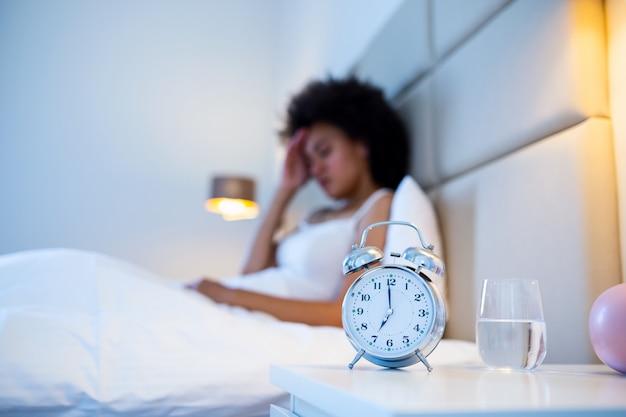 Młoda kobieta w sypialni w domu, leżąca w łóżku późno w nocy, próbująca zasnąć, cierpiąca na bezsenność, zaburzenia snu lub boi się koszmarów, wyglądająca na smutną zmartwioną i zestresowaną