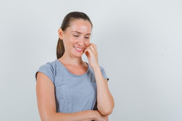 Młoda kobieta w szarej koszulce patrząc w dół, uśmiechając się i patrząc z nadzieją, widok z przodu.