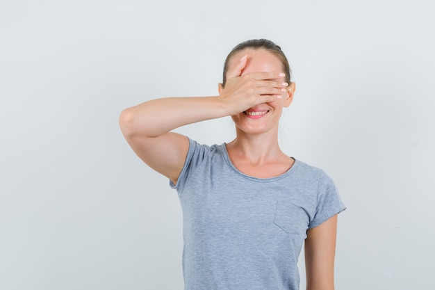 Młoda kobieta w szarej koszulce trzymając rękę na oczach i patrząc podekscytowany, widok z przodu.