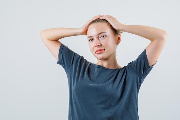 Młoda kobieta w szarej koszulce, trzymając się za ręce na głowie i uśmiechając się