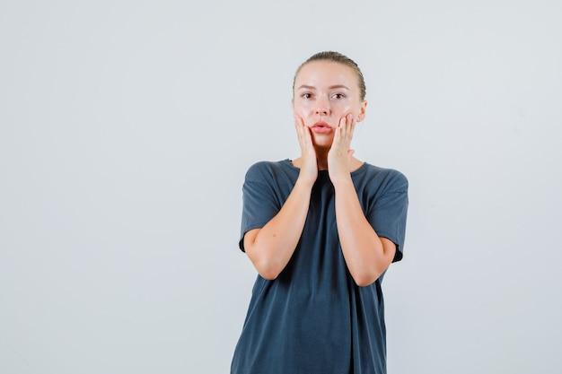 Młoda kobieta w szarej koszulce, trzymając się za ręce na policzkach i patrząc zdziwiony
