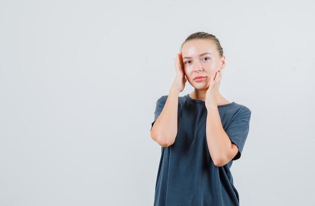 Młoda kobieta w szarej koszulce z rękami na twarzy i ładnie wyglądający