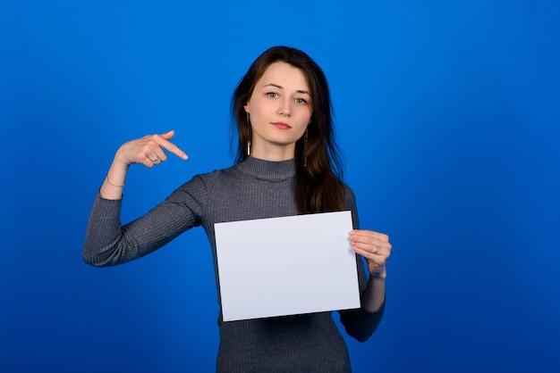 Młoda kobieta w szarej koszuli trzyma kartkę papieru i patrząc w kamerę, uśmiechając się. niebieskie tło na białym tle
