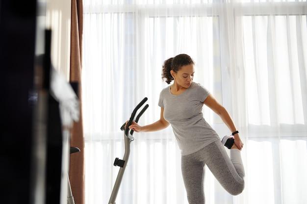 Młoda kobieta w szarej odzieży sportowej, rozciągając mięśnie nóg po treningu w domu, ucząc się jej ręki za rowerem stacjonarnym
