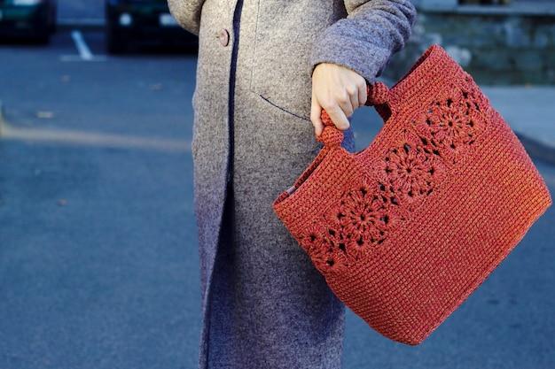 Młoda kobieta w szarym ciepłym płaszczu idzie na ulicę miasta z czerwoną torbą z dzianiny city lifestyle