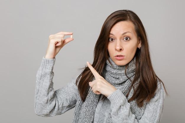 Młoda kobieta w szarym swetrze, szalik wskazując palcem na tabletki aspiryny tabletki leków na białym tle na tle szarej ścianie w studio. zdrowy styl życia chory chory choroba leczenie koncepcja zimnej pory roku.