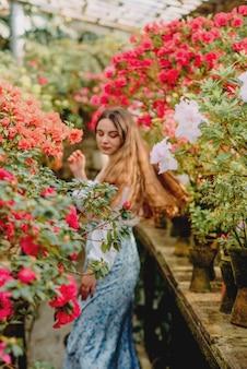 Młoda kobieta w szklarni z azaliami