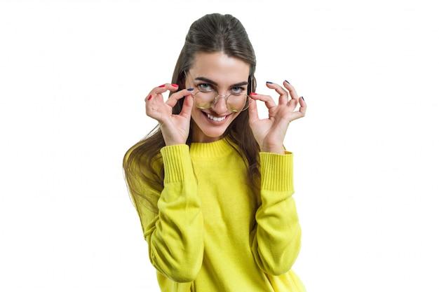Młoda kobieta w szkło koloru żółtego ubraniach na bielu odizolowywającym