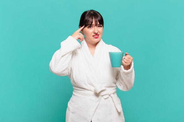 Młoda kobieta w szlafroku czuje się zdezorientowana i zdezorientowana, pokazując, że jesteś szalony, szalony lub oszalały