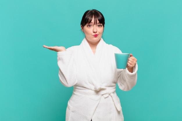 Młoda kobieta w szlafroku czuje się zdziwiona i zdezorientowana, wątpi, waży lub wybiera różne opcje ze śmiesznym wyrazem twarzy