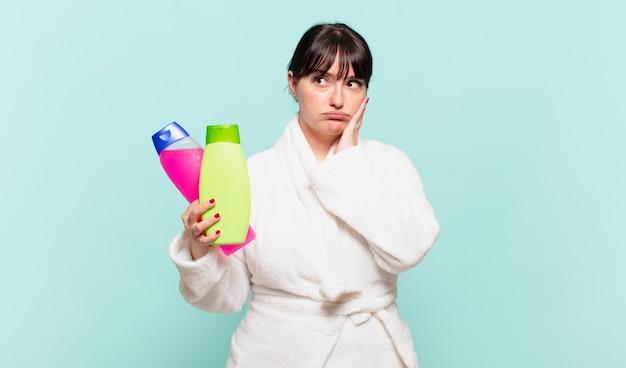 Młoda kobieta w szlafroku czuje się znudzona, sfrustrowana i senna po męczącym, nudnym i żmudnym zadaniu, trzymając twarz dłonią