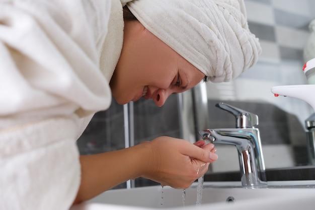 Młoda kobieta w szlafroku i ręczniku myjąca twarz wodą