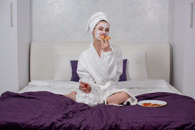 Młoda kobieta w szlafroku i ręczniku pysznie je pizzę i pije wino siedząc w domu na łóżku wysokiej jakości zdjęcie