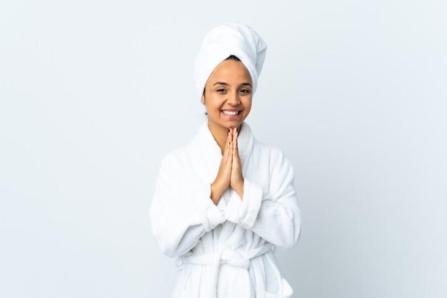 Młoda kobieta w szlafroku na białym tle trzyma dłoń razem. osoba o coś prosi