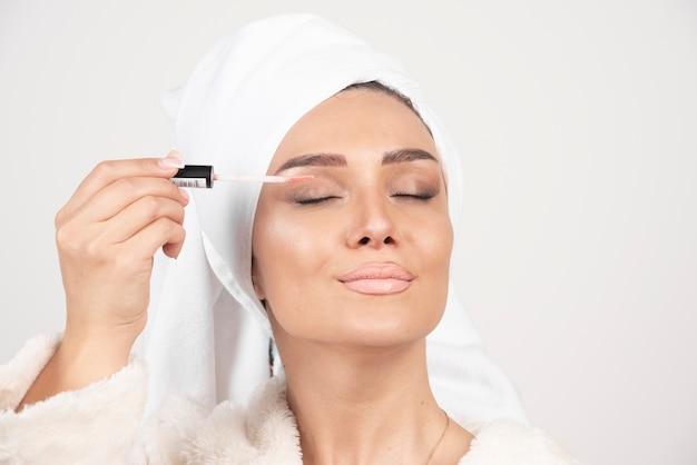 Młoda kobieta w szlafroku, nakładając szminkę na powieki.