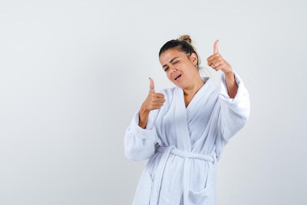 Młoda kobieta w szlafroku pokazująca kciuki do góry i wyglądająca pewnie