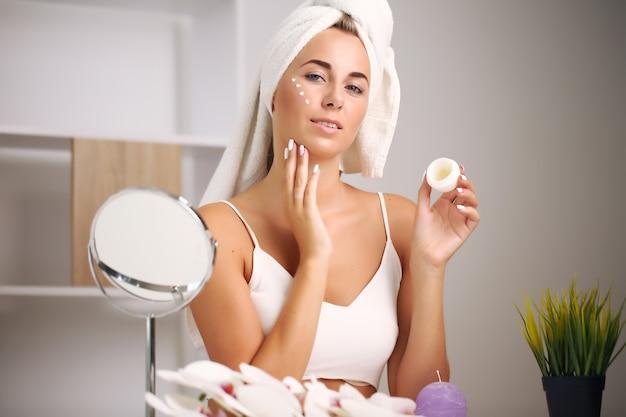 Młoda kobieta w szlafroku, przynosi piękno w łazience