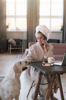 Młoda kobieta w szlafroku rozmawia przez telefon komórkowy, siedząc przy stole z laptopem w domu
