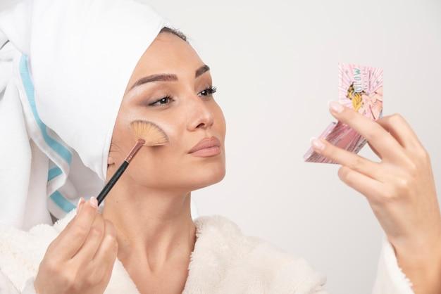 Młoda kobieta w szlafroku trzymając pędzel do makijażu.