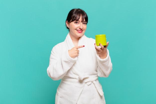 Młoda kobieta w szlafroku uśmiecha się radośnie, czuje się szczęśliwa i wskazuje na bok i do góry, pokazując obiekt w przestrzeni kopii