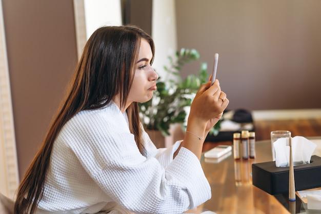 Młoda kobieta w szlafroku w pokoju hotelowym przy użyciu telefonu komórkowego