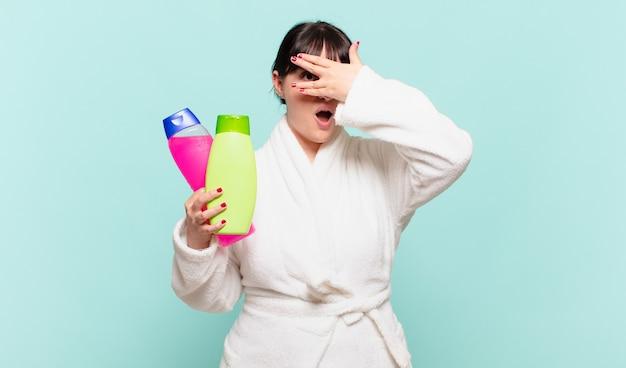 Młoda kobieta w szlafroku, wyglądająca na zszokowaną, przestraszoną lub przerażoną, zakrywa twarz dłonią i zerka między palcami