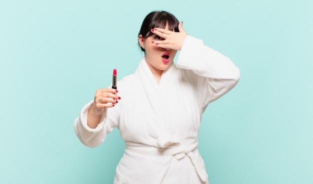Młoda kobieta w szlafroku wyglądająca na zszokowaną, przestraszoną lub przerażoną, zakrywającą twarz dłonią i zerkającą między palcami